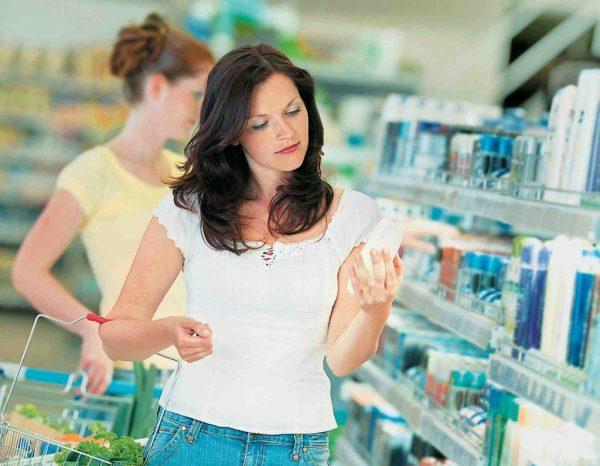 Девушка рассматривает крем в магазине
