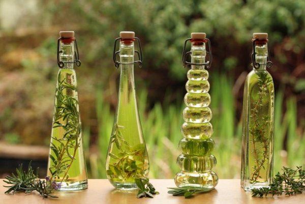 Бутылки с маслом и растениями в нём