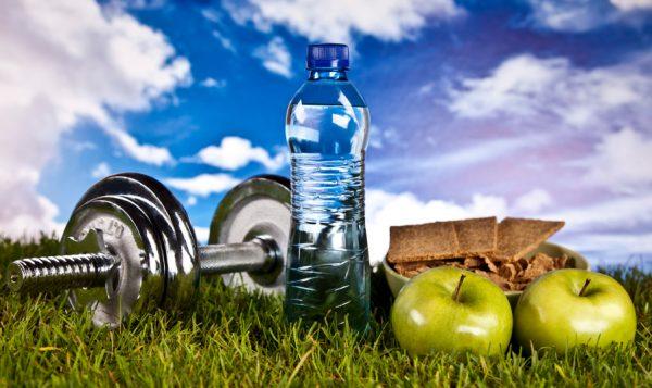 Гантель, вода, яблоки и хлебцы на траве