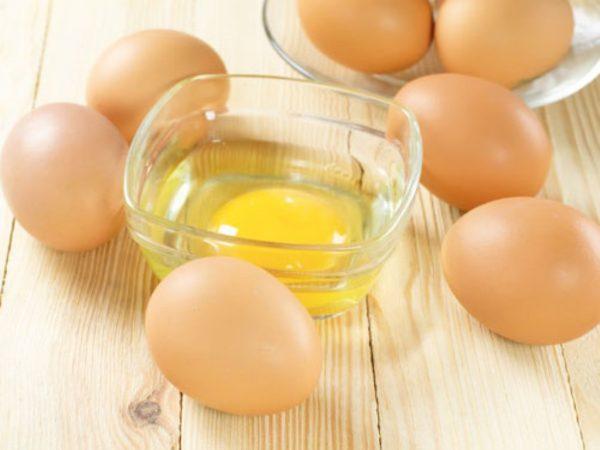 Целые яица и разбитое яйцо в миске