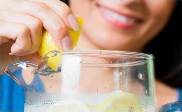 Девушка добавляет сок лимона в воду