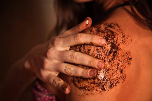Девушка скрабирует кожу молотым кофе
