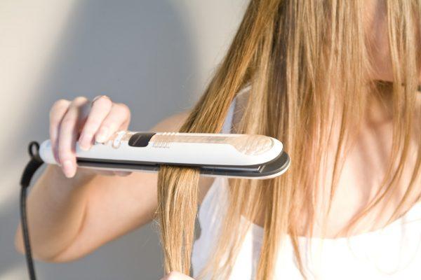 Девушка выпрямляет волосы утюжком