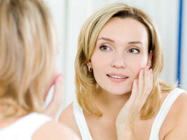 Женщина смотрится в зеркало