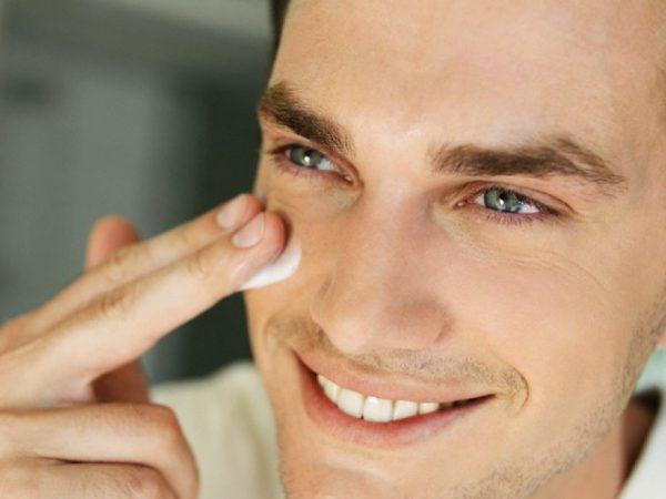 Мужчиа наносит крем на лицо