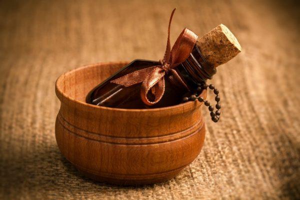 Бутылочка из тёмного стекла, перевязанная коричневой декоративной лентой, лежит в деревянной круглой коробочке