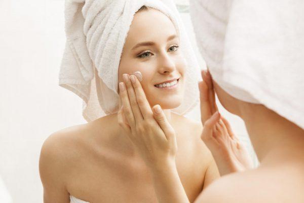 Девушка в полотенце на голове мажется кремом