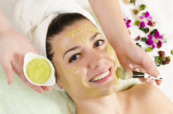 Девушке на лицо наносят косметическую маску