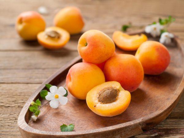 Спелые абрикосы на деревянной тарелке