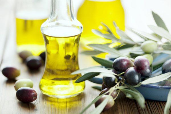 Базовое оливковое масло в прозрачном флаконе и оливки на деревянном столе