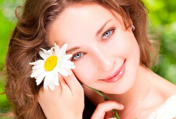 Девушка с голубыми глазами с ромашкой в руках