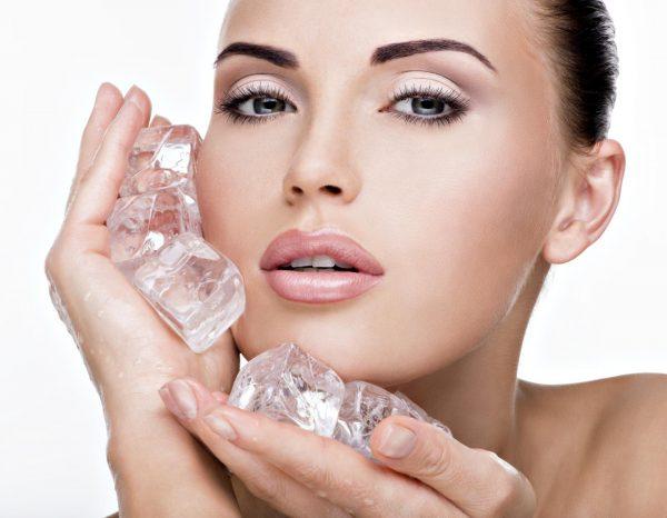Девушка держит у лица кубики льда