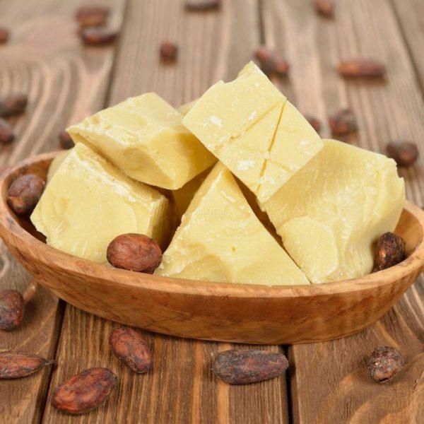 Масло и бобы какао в деревянной миске на столе