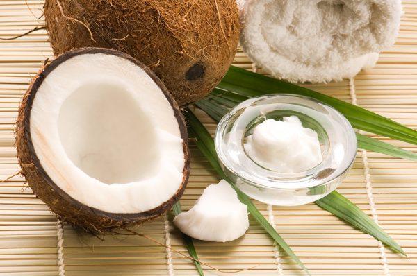 Орех кокоса и кокосовое масло в стеклянной мисочке