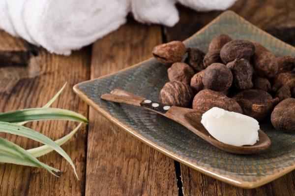 Масло ши на деревянной ложке и плоды одноимённого дерева на плоской тарелке