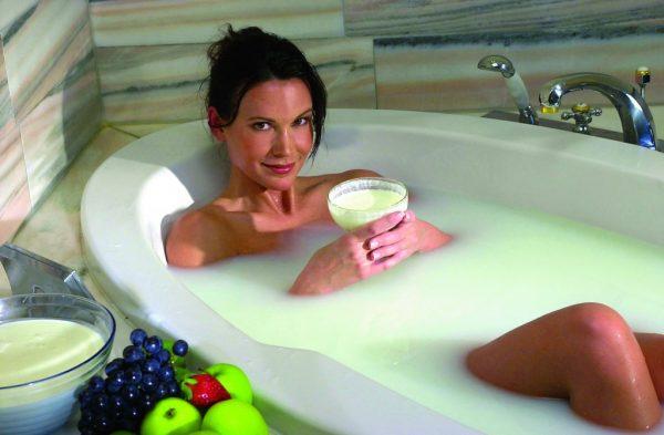 Девушка в молочной ванне с бокалом в руках