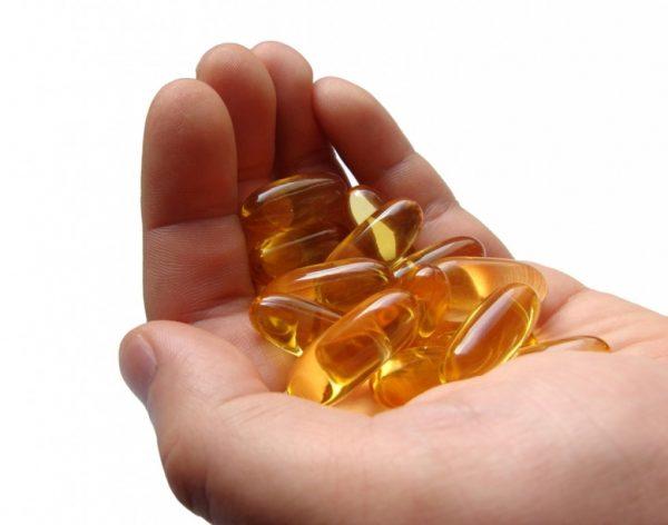 Витамины в капсулах на ладони