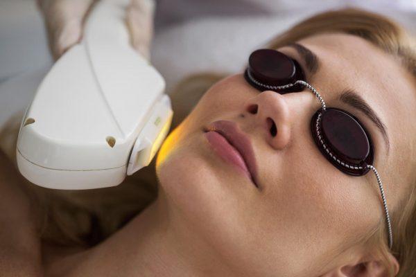 Женщина лежит в специальных очках для процедуры фотоомоложения