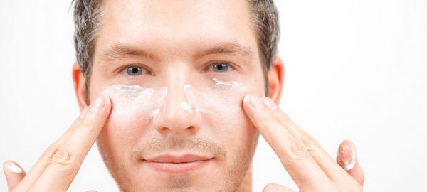 мужчина наосит крем на лицо