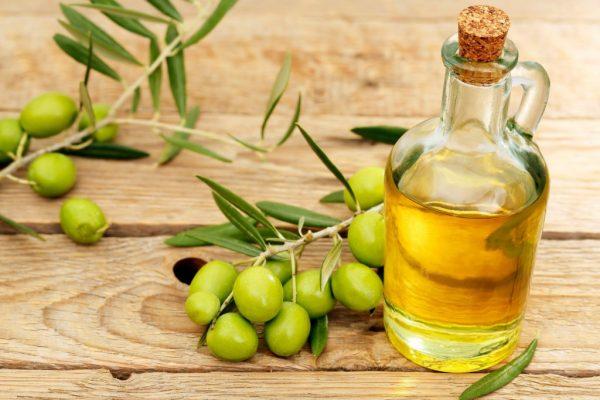 Плоды оливы и оливковое масло в прозрачной баночке на столе