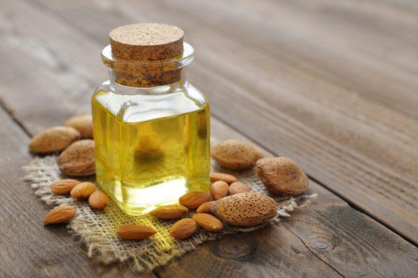 Миндальное масло в прозрачной баночке стоит на столе