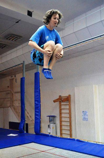Девушка прыгает и группируется на батуте