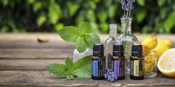 Эфирные масла в бутыльках, мята, лаванда и лимон на деревянном столе