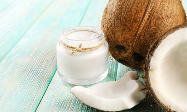 Кокосовое масло и кокос на голубом деревянном столе