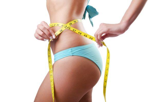 Девушка сантиметровой лентой измеряет талию