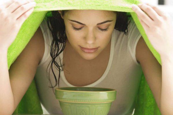 Девушка с полотенцем над чашей распаривает лицо