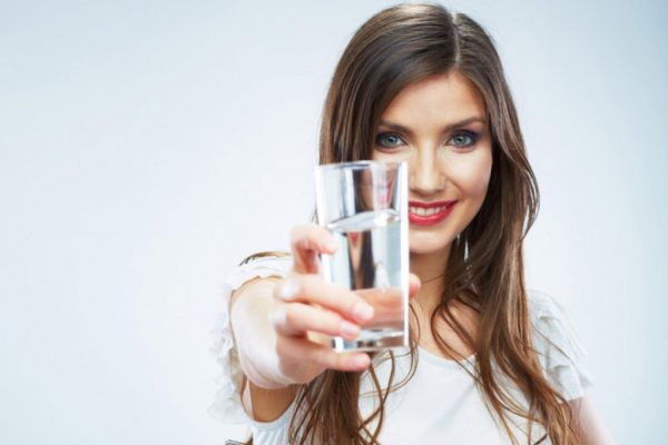Девушка держит стакан с водой