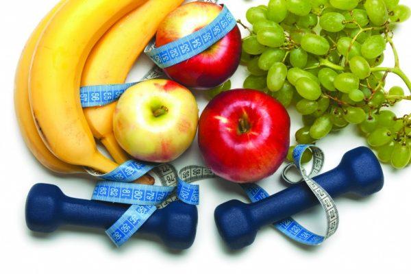 Бананы, яблоки, виноград, измерительная лента и гантели