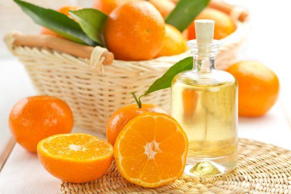 Бутылочка апельсинового масла и несколько апельсинов