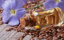 Бутылка масла рядом с цветком и семенами льна