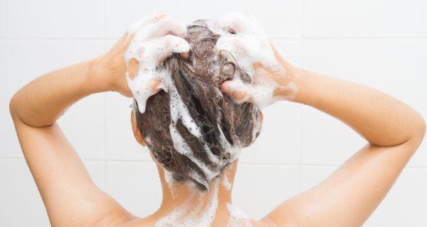 Девушка наносит шампунь на волосы