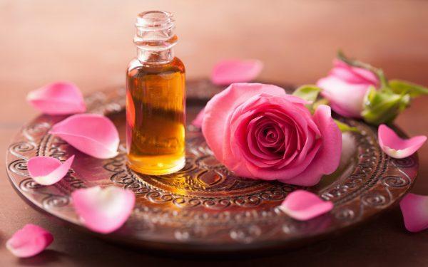 Эфирное масло розы и цветок розы на подносе
