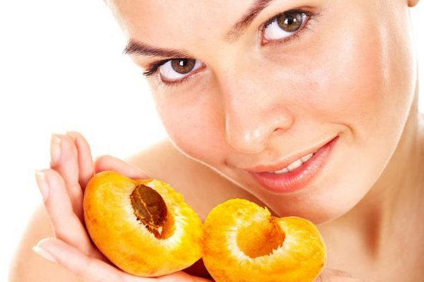 Лицо девушки и половинки абрикоса в руках