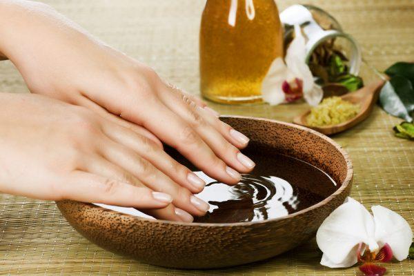 Красивые руки и ванночка с маслом