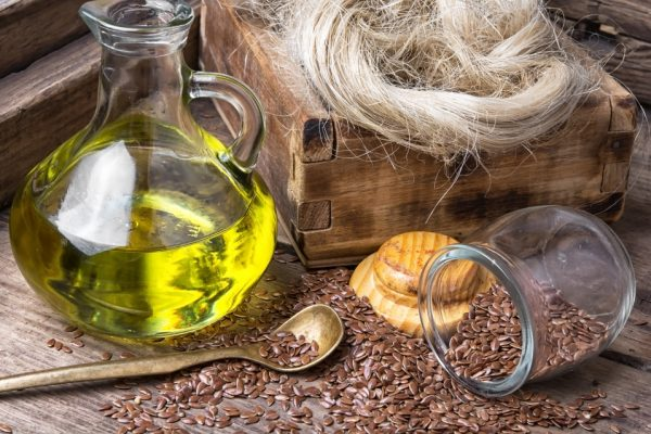 Льняное масло, ложка, баночка и россыпь семян льна