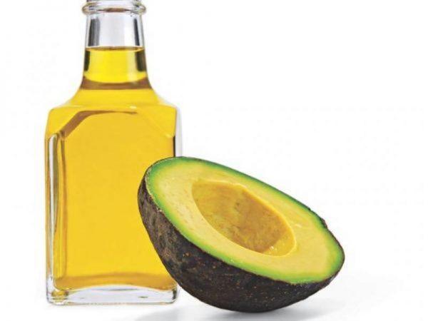 Масло и половинка плода авокадо