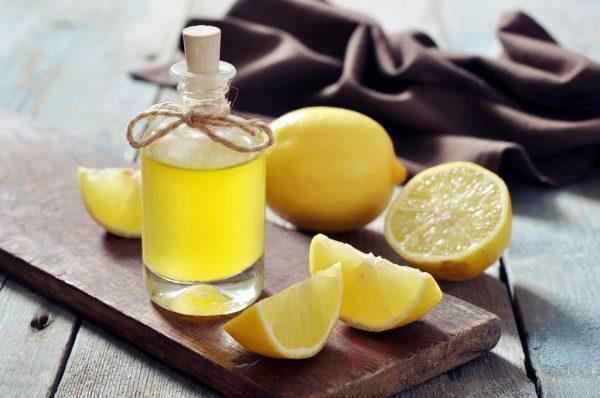 Лимоны и бутылка с лимонным соком на столе