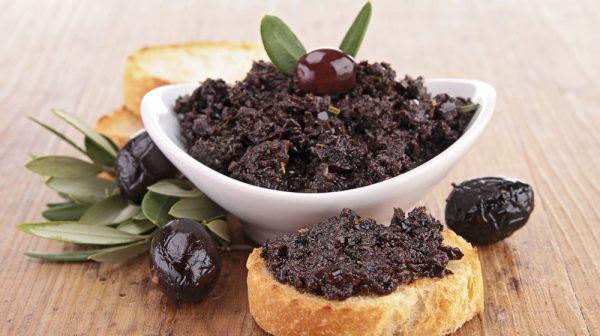 Оливковый тапенад в тарелке и на хлебе