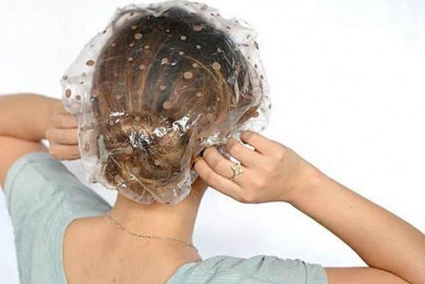 Девушка надевает полиэтиленовую шапочку на волосы