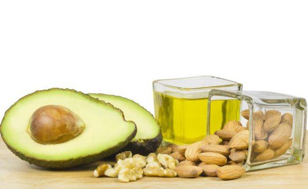 Плод авокадо рядом с орехами и стаканом масла