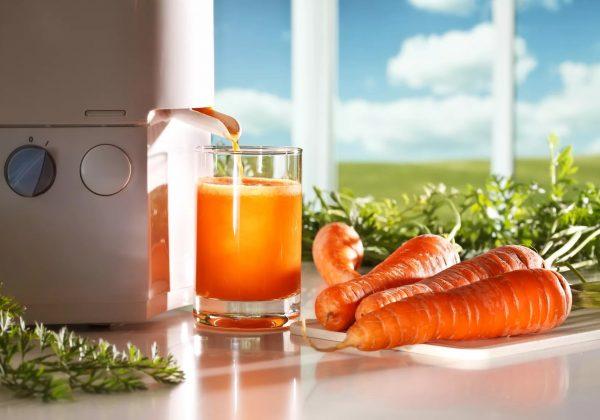 Соковыжималка делает морковный сок