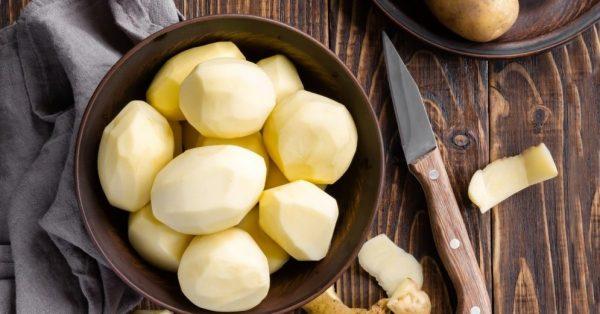 Сырой очищенный картофель в миске