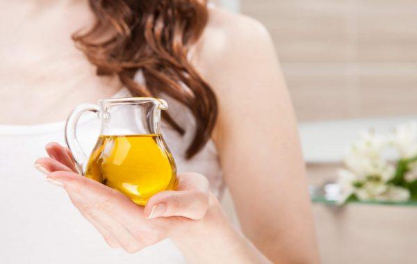 Женщина держит кувшинчик с маслом