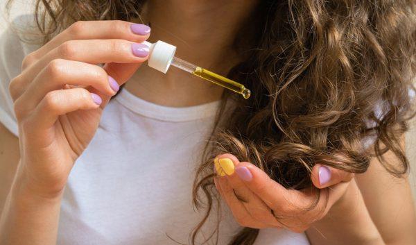Девушка капает масло на волосы из пипетки