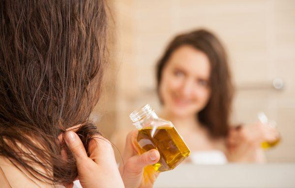 Девушка мажет волосы маслом