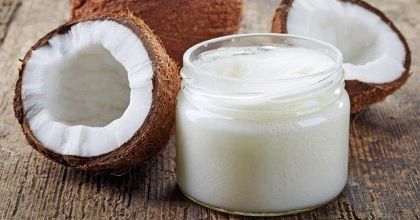 Кокосовое масло в прозрачной банке и плоды в разрезе